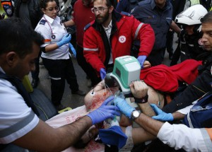 Israeliska sjukvårdare ge akutvård till ett offer efter en attack av en oidentifierad beväpnad man, som öppnade eld på en pub i den israeliska staden Tel Aviv dödade två personer och skadade fem andra den 1 januari 2016. AFP PHOTO / JACK Guez