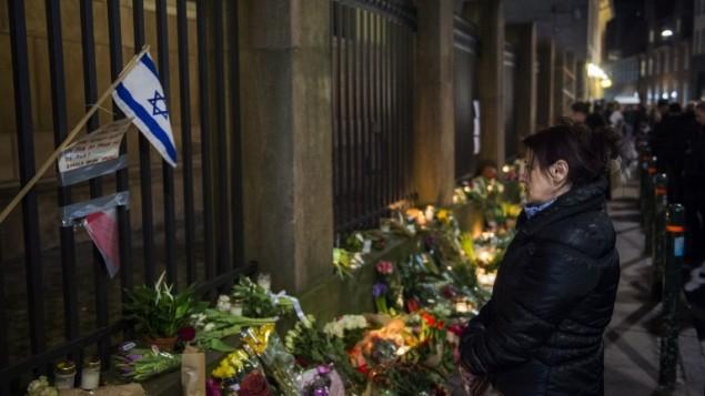 Gönnern reagiert, wie sie Blumen und Kerzen bringen die Aufnahme Opfer außerhalb der Haupt-Synagoge in Kopenhagen, Dänemark, am 15. Februar zu Ehren 2015