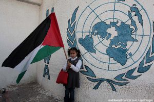 palestinian-girl-with-flag-in-front-on-unrwa-logo
