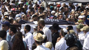 Thousands of mourners attend the funerals of murdered Rabbi Eitam Henkin, 31, and his wife Na'ama, 30, in Jerusalem.